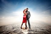 foto of loving_couple  - Happy young couple standing on water - JPG