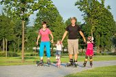image of family fun  - Parents and two daughters skating in a summer park - JPG