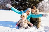 Young family of three throwing snow