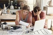 Young Couple Doing Paperwork In Kitchen: Frustrated Woman Reading Document Together With Her Husband poster