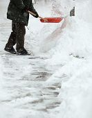 foto of snow shovel  - Man shoveling snow from the sidewalk in front of his house after a heavy snowfall in a city - JPG