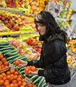 stock photo of grocery-shopping  - Beautiful young woman buying fruits and vegetables at a supermarket - JPG