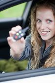 Pretty young woman showing off her brand new car - showing you the car keys poster