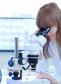 pretty female researcher using a microscope in a lab