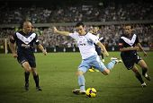 MELBOURNE - MARCH 20: Mark Bridge (C) of Sydney FC crosses the ball in the A-League grand final agai