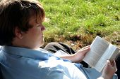 Teen Engrossed In Book Outdoors poster