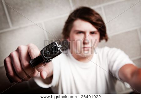 teenager male pointing gun at camera