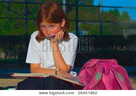Schoolgirl in uniform is sitting with open book and pencil. She is learning. the book is on her lap.