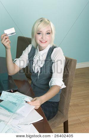Amistoso Rubio sting mujer caucásica por mesa con ordenador portátil y sosteniendo la tarjeta de crédito a pagar h