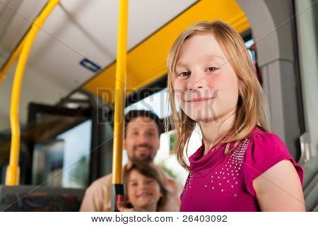 Child in a bus; in the background presumably her father and sister to be seen