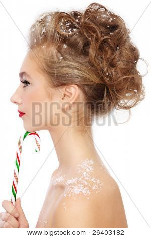 Profile of young beautiful girl with fancy stylish hairdo and candy cane in hand, over white background