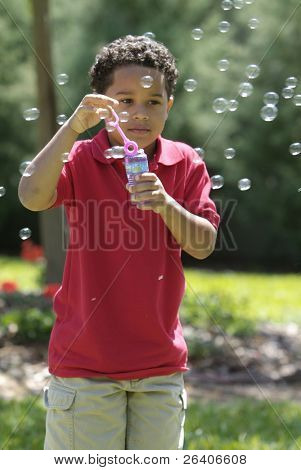 Boy blowing bubbles at the park