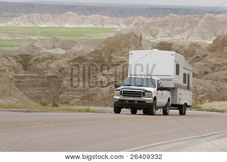 RV pick-up truck and trailer climbing scenic mountain road in the Badlands