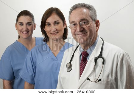 Two hispanic nurses on white background with mature male doctor
