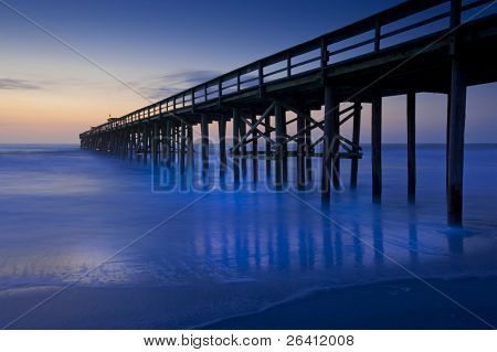 Rich blue sunrise ocean beach pier motion blur