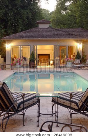 Two lounge chairs over look an inviting pool and a pool house