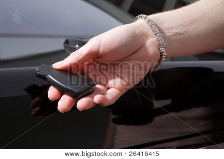 A woman unlocking her car wearing a diamond tennis bracelet