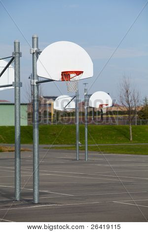 A row of basketball hoops on a blacktop