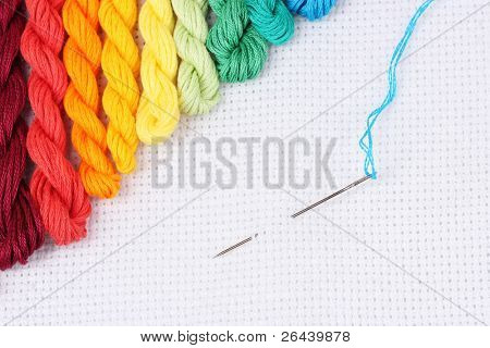 sewing threads for embroidery and  needle with a thread on white cotton