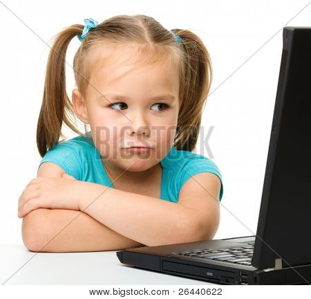 Niña ofendida está sentado en la mesa con su ordenador portátil negro, aislado en blanco
