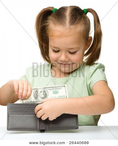 Cute little girl is putting dollars in purse, isolated over white