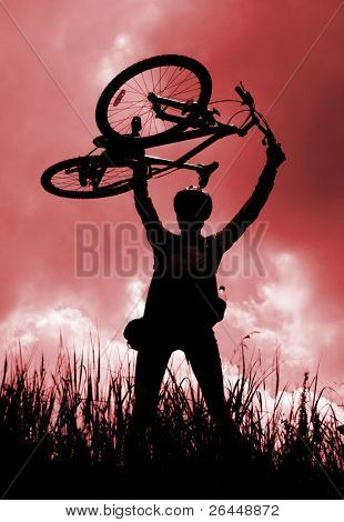 Silhouette of a biker holding his bicycle, red tint