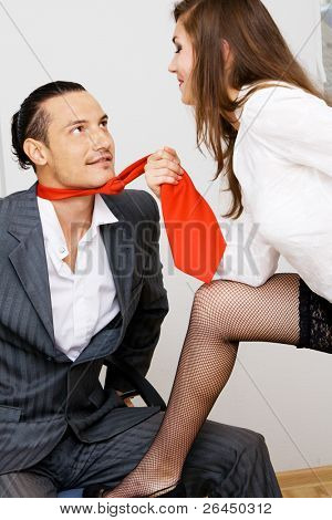 Young businessman and businesswoman flirting in office