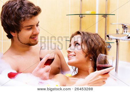 Young couple drinking red wine in bath