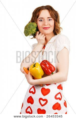 Beautiful housewife with a bunch of fresh vegetables, white background