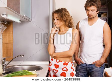 Young couple in kitchen, looking frustrated