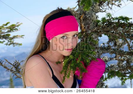 Beautiful Young Woman Standing By A Tree