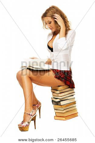 Sexy student girl sitting on a stack of books against white background