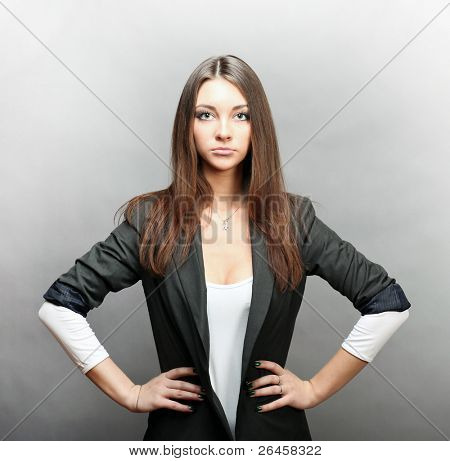serious woman in business suit put hands on hips