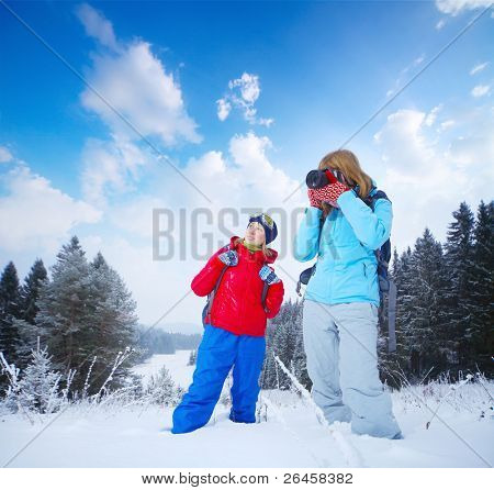 Young women with backpacks standing in a snowy field. One is smiling another one taking shoot with a camera.
