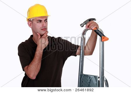Doubtful man holding a hammer and a ladder