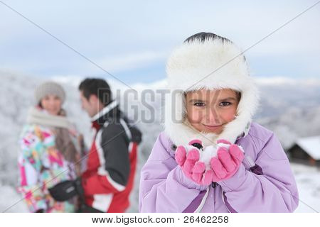 Little girl playing in the snow with her parents