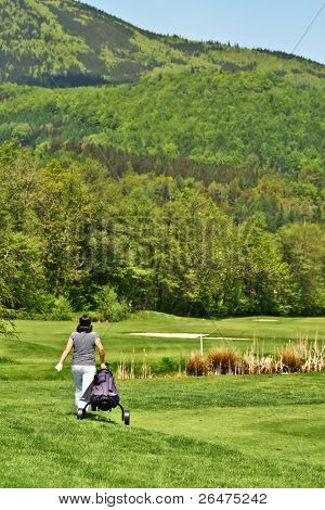 Golfer on golfcourse with golf bag