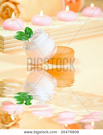 Moisturizing cream with candles and towel and reflection