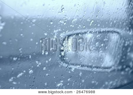 Droplets and snowflakes on car window and rear view mirror