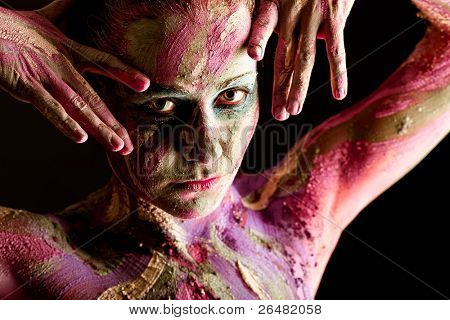 Portrait of an artistic woman painted with clay. Shot in a studio over black background.