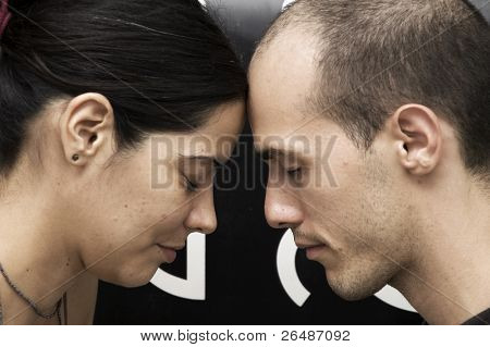 Strong connection - Portrait of a young couple head to head meditating with eyes closed