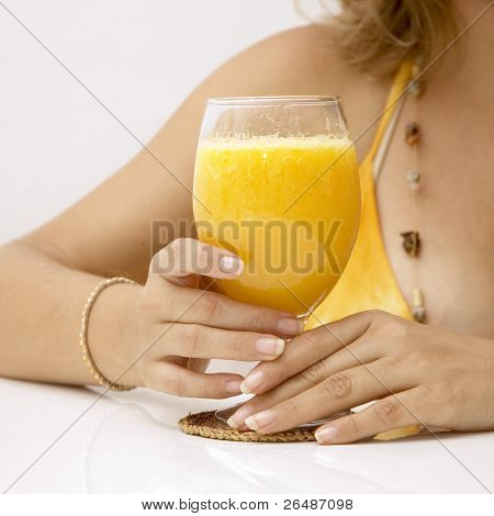 Detail of woman hands on orange juice glass