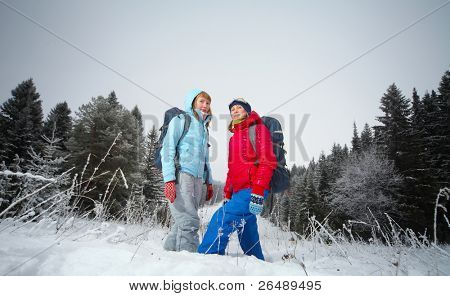 Young women with backpacks standing in a snowy field
