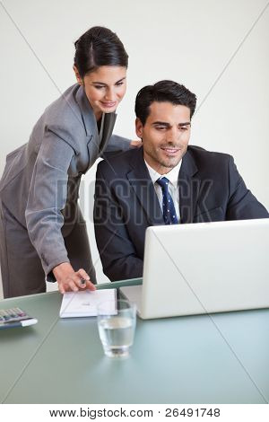 Portrait of sales persons working with a laptop in an office