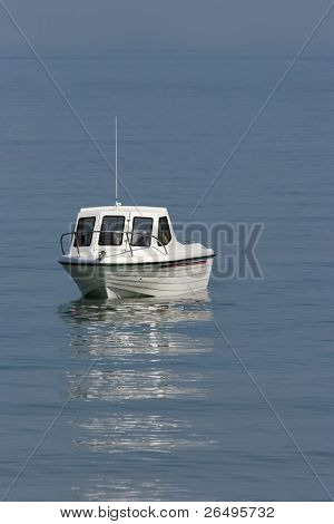 White motor cruiser on a calm blue sea.