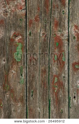 Old oak wooden planks with remnants of red and green paint.