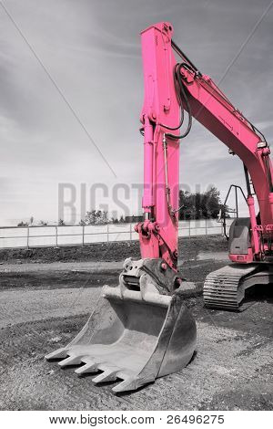 Steel excavator bucket on a pink industrial digger, standing idle on hardcore. Desaturated with only the digger in color.