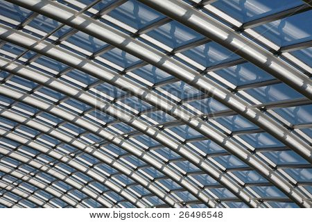 Conservatory roof span with curved metal joists and glass window panes against a blue sky.