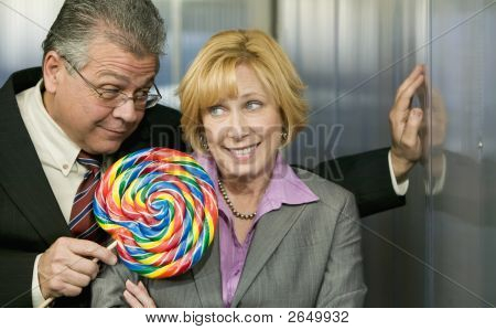 Man In Office Offers Coworker A Lollipop