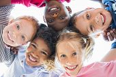 Closeup face of happy multiethnic children embracing each other and smiling at camera. Team of smili poster